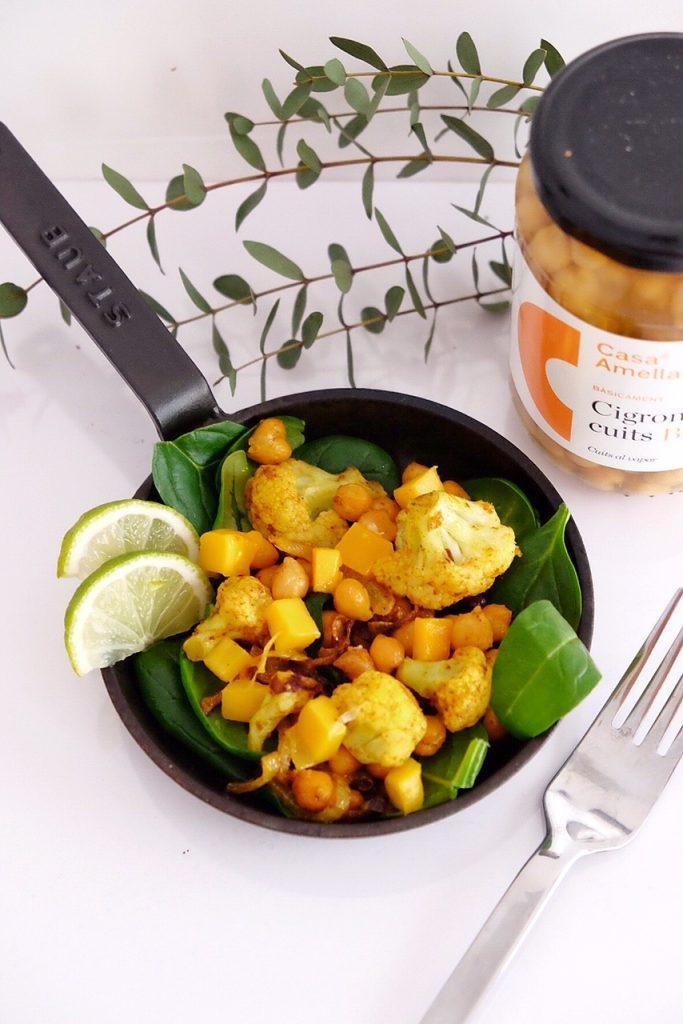 Amanida tèbia de cigrons, coliflor amb curri, espinacs crus i mango